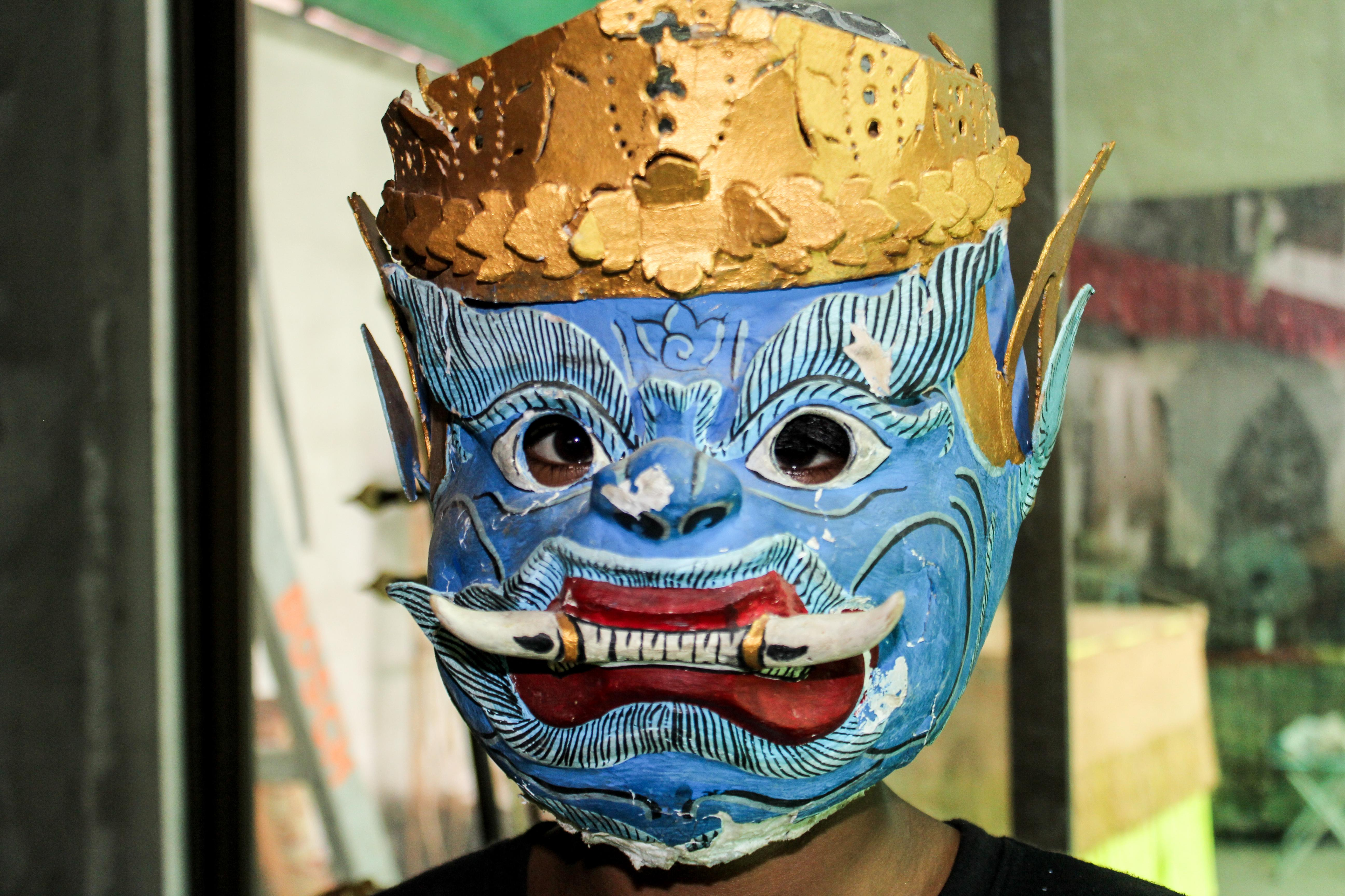 A volunteer over 50 learning about the Khmer culture in Cambodia, wears a traditional mask.